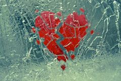 Broken heart in shattered ice.. Broken red heart with pieces breaking off in in ice that is shattering Stock Photo