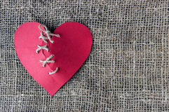 A broken red heart. Sewn thread. The concept of divorce, separation. stock images