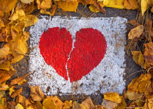 Broken red heart in white rectangle. Broken red heart painted on the road in a dry leaves frame stock images