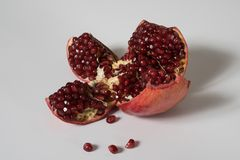 Broken red ripe pomegranate on white table royalty free stock photos
