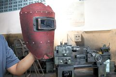 Broken Red welding mask in the man hand. In factory Royalty Free Stock Photography