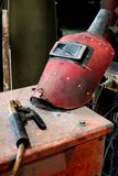 Broken Red welding mask with wire clamp instrument. In factory Stock Images