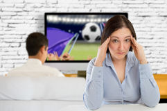 Broken relationship. Stressed women sitting at the home with hands on head because her husband sees a lot of football on TV Royalty Free Stock Image