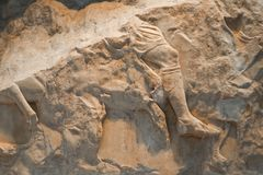 Broken remnant of Greek carving of mans leg on horse - Background or element. The Broken remnant of Greek carving of mans leg on horse - Background or element Stock Image