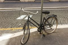 Broken retro bicycle with deflated and damaged wheel, enchained to the light pillar in the street of Rome royalty free stock photo