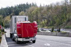 Broken on the road big rig red semi truck with an open hood. A large professional red big rig semi truck with reefer trailer broke engine on the road and Stock Photo