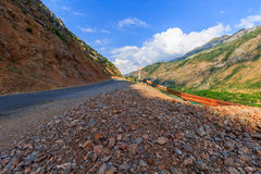 The broken road in the mountains and the dangerous bend sign. Royalty Free Stock Photography