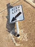 Broken road sign at a traffic island, bent to the ground after heavy impact Stock Photo