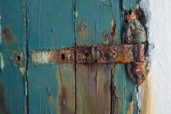 A broken rusting door hinge on a painted wooden door, paint peeling off the wood royalty free stock photo