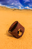 Broken rusty can on sand Stock Images