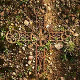 Broken and rusty iron rustic crucifix on old mossy tombstone. Abandoned symbol of religion. Stock Photography