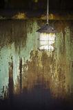Broken and rusty lamp. In front of rusty steel Stock Photos