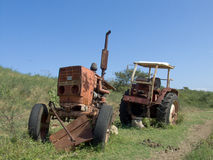 Broken rusty tractor on farm. Broken rusty old tractor on green field in countryside with blue sky background Stock Photos