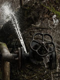 Broken Rusty Valve. A broken rusty valve that leaks and gushes water Stock Photography