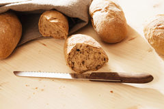 Broken rye bun with a knife Stock Images