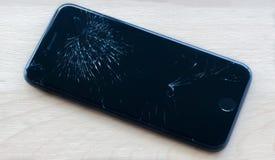 Broken sartphone close-up. Black broken smartphone lying on the table Stock Photo