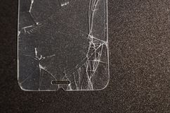 Broken screen of a phone. On the black background. Need to repair and fix concept. Crashed phone glass cover close up view royalty free stock photography