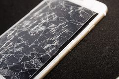 Broken screen of a phone. Isolated on the black background. Need to repair and fix concept. Crashed phone glass cover close up view stock photos