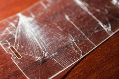 Broken screen of a phone. On the wooden table. Need to repair and fix concept. Crashed phone glass cover close up view stock photo