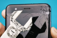 Broken screen of the phone in hand and dollar in the form of a key, as a concept on cost of repairing a mobile device. Close-up royalty free stock image
