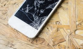 Broken screen phone on wood table. With copy space for text. technology concept stock image