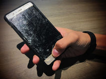 Broken screen of a smart phone. On owner hand stock photos