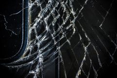 The broken screen of the smartphone close up, you can see the cracks of the glass and shards.  stock image