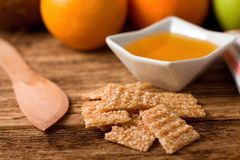 Broken sesame wafers in front of bowl with honey Stock Images