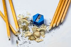 Broken and sharpened pencils with sharpener. And shavings on white paper Stock Photos