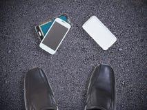 Broken smart phone on concrete floor between owner`s shoes. Broken smart phone after being dropped on concrete floor between owner`s man shoes royalty free stock photography