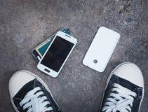 Broken smart phone on concrete floor between owner`s sneaker sho. Broken smart phone after being dropped on concrete grunge floor between owner`s sneaker shoes royalty free stock photos
