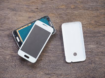 Broken smart phone on wood background. Broken smart phone on the grunge wood background royalty free stock photo