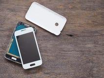 Broken smart phone on wood background. Broken smart phone on the grunge wood background royalty free stock image