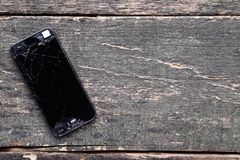 Broken smartphone. On grey wooden table stock photography