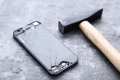 Broken smartphone. With hammer on wooden table stock photo