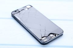 Broken smartphone. On wooden table stock photos