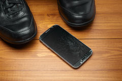 Broken smartphone dropped on shoes Royalty Free Stock Photography
