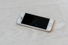 Broken smartphone lies on the white floor close-up stock images