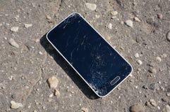 Broken smartphone screen on ground. Broken smartphone screen on the ground stock photo