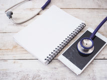 Broken smartphone with stethoscope and notebook on wooden background stock photos