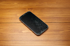 Broken smartphone on table in wood Stock Images