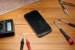 Broken smartphone with tools Royalty Free Stock Image