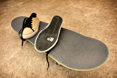 Broken sneakers on a skateboard Stock Image