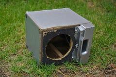 Broken speaker dumped on green grass stock photo