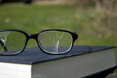 Broken Specs. A close-up photograph of a pair of broken spectacles on top of a book. Shot under natural sunlight with plenty of copyspace Stock Photos