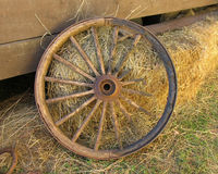 Broken Stagecoach Wheel, Landscape View (Centered). An old, broken stagecoach wheel leading against a wooden shack Royalty Free Stock Photo
