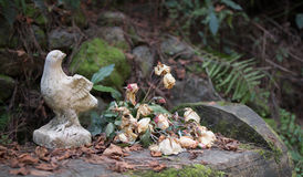 Broken statuette of a bird and bouquet of wilted flowers. On the garden bench Royalty Free Stock Photo
