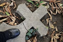 Broken stone cemetery cross lying on ground with black leather boot standing on it Royalty Free Stock Photos