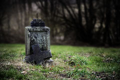 Broken stone cross, weathered gravestone on an old abandoned cem. Etery, concept for transience or gloomy halloween background with copy space Stock Image
