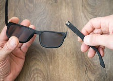 Broken sun glasses in the hands royalty free stock photography